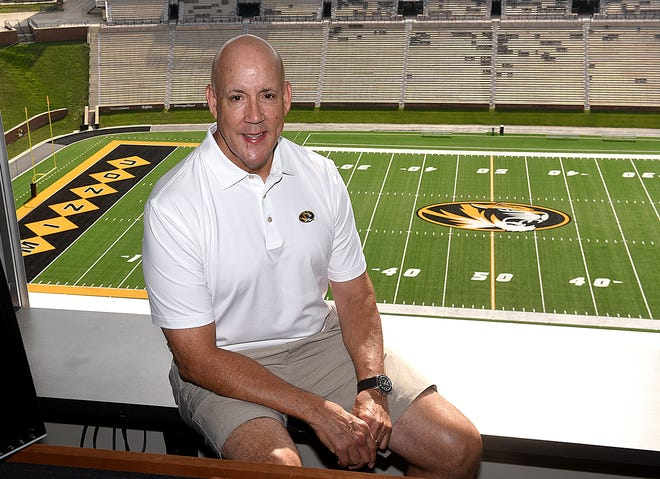 Mike Kelly, voice of the Missouri Tigers, poses for a photo in his work area at Memorial Stadium overlooking Faurot Field.