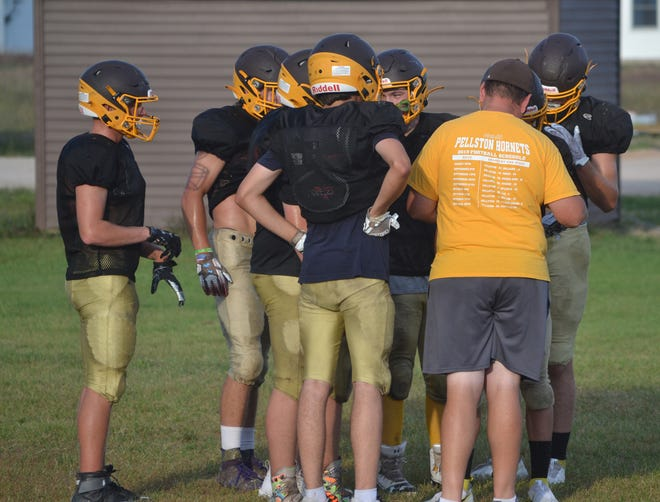 Pellston offensive players and coaches huddle up during a practice in August. The Hornets will host Hale on Friday night.