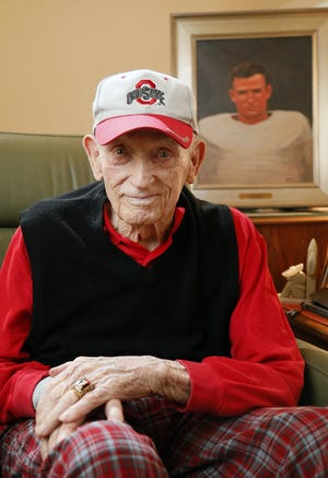 """Cecil """"Cy"""" Souders, a lineman on the 1942 Ohio State Buckeyes national champion football team, sits in front of his Ohio State Athletic Hall of Fame portrait in his Hilliard-area apartment on Jan. 24, 2020."""