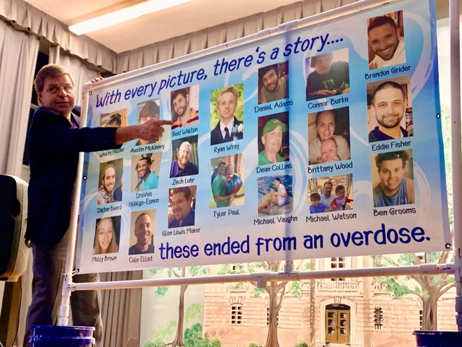 Pastor John Walton of First Family Church points to his son Reid's picture as part of a banner displaying the faces and names of Maury County overdose victims.