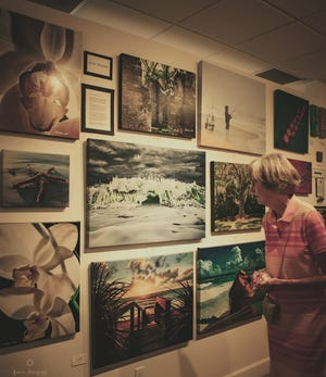 A woman views some of the paintings and photos during a previous Ormond Art Walk.