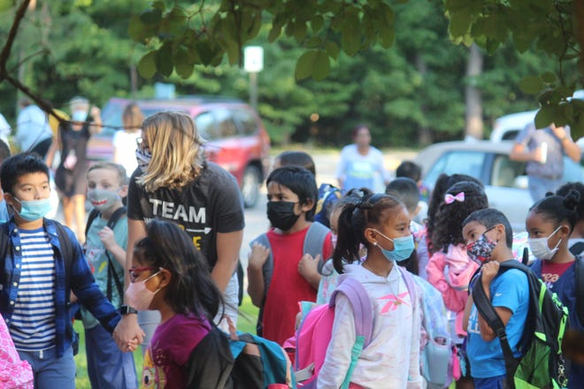 Students arrive for school at Pine Creek Elementary School on Wednesday, Sept. 1, in Holland, Mich. Ottawa County health officials have asked school administrators to report whether they are enforcing the K-6 mask order.