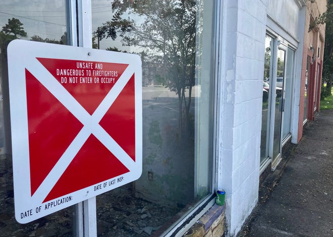 A sign on a downtown Jacksonville building located on New Bridge Street says it is unsafe and dangerous to firefighters.