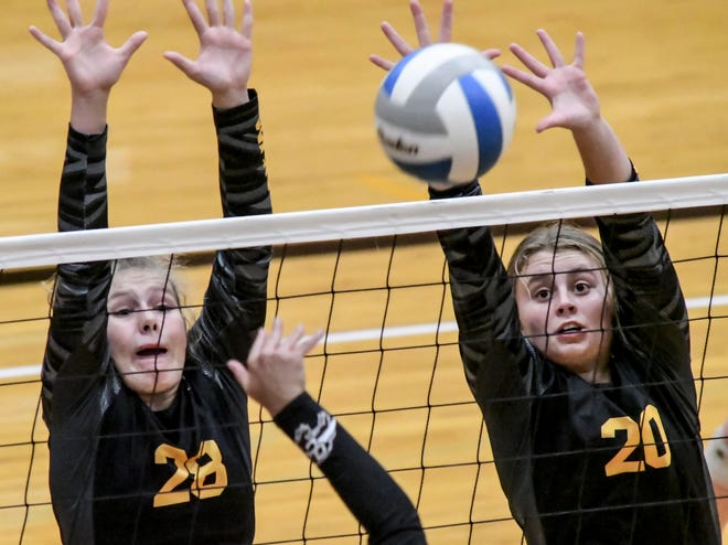Newton's Lana Mayfield, right, knocks a Garden City shot back down onto the Buffaloes side as she and Camryn Entz go up for a block Tuesday during a volleyball triangular match in Garden City.