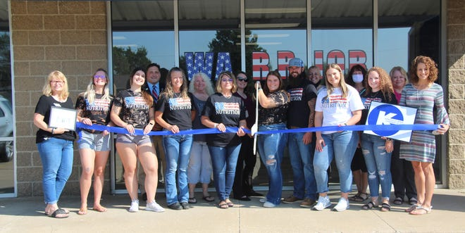 Emily Akey, the owner of Warrior Nutrition in Kirksville, cuts a ribbon during a ceremony outside the store on Wednesday, Sept. 1.