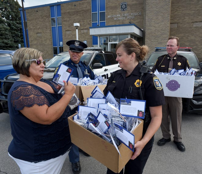 """Shelly Griffin with Scentsy put together 200 scent bags are given to the City of Monroe Lt. Terese Herrick, Michigan State Trooper Don Stewart and Monroe County Sheriff deputy chief Dave Buchko to pass out to their troopers for their vehicles. Their was several sponsors who help pay for the bag which cost 10 dollars each. """"I wanted to do something special for our police,"""" said Griffin."""