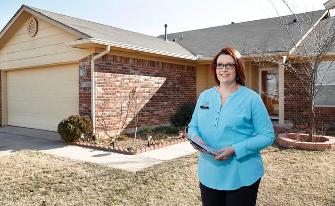 Kathy Fowler stands outside a house she had listed for sale in southwest Oklahoma City.