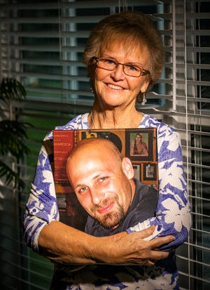 Cheryl Dungan, chapter leader of the Central Florida Chapter of the Compassionate Friends, hugs a portrait of her son Ryan Von Gogh, 28, while at her home in Summerfield on Wednesday. He suffered a traumatic brain injury from a motorcycle accident and died in 2006 in hospice care after Cheryl took care of her son for some time after the accident. The group, for parents who have lost a son or daughter, will meet every second Thursday of the month at Trinity Lutheran Church in Summerfield.