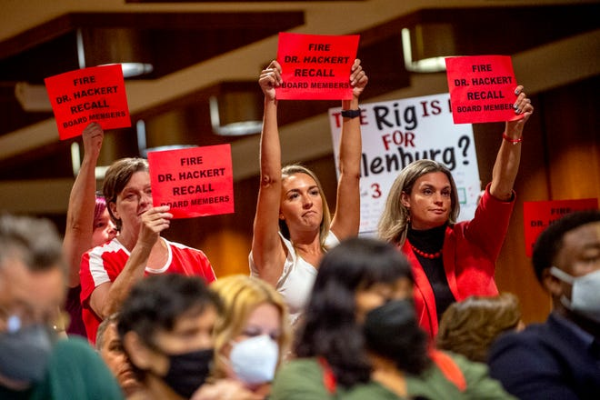 Parents and residents stand to oppose the county's K-6 school mask mandate after public comment finished as more than 100 people pack the Harris Auditorium at a Genesee County Board of Commissioners meeting on Monday, Aug. 30, 2021 at the county administration building in downtown Flint, Mich. (Jake May/The Flint Journal via AP)