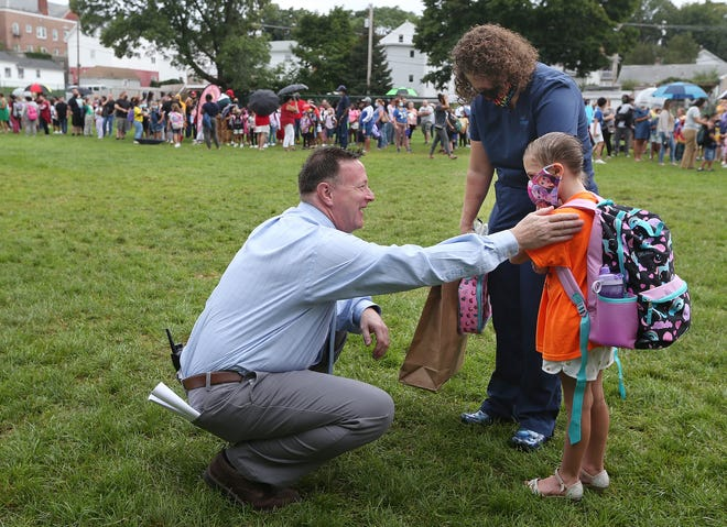 Michael Gilmore, principal of Agnes E. Little Elementary School in Pawtucket, welcomes new student Emmerson Fisher, 5, and her mother, Nicci Fisher, before the students entered the school for the new year.