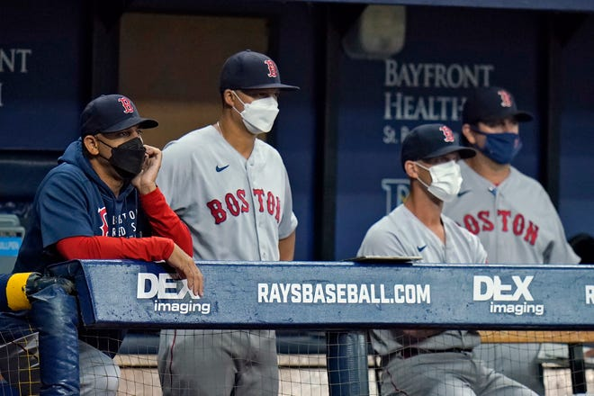 With a new breakout of COVID cases among Red Sox players, manager Alex Cora, left, and members of his coaching staff are back to wearing masks in the dugout during games this week against the Tampa Bay Rays in Florida.