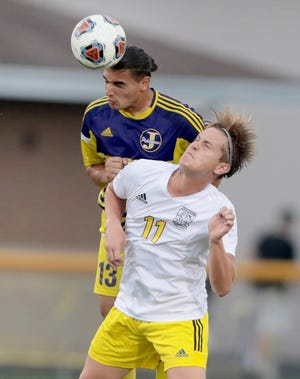 Jackson's AJ Jaber, left,heads the ball away from Perry's Steve Bossler in the first half of their matchup at Jackson Tuesday, August 31, 2021.