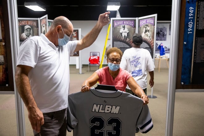 """Carolyn Farrar, center, president of the Springfield and Central Illinois African American History Museum, arranges a Homestead Grays replica jersey from the Negro Baseball Leagues with the assistance of Paul Countryman, exhibits lead at the Illinois State Museum, as they work to set up the new exhibit at the Springfield and Central Illinois African American History Museum in Springfield on Aug. 30. The traveling exhibit """"Negro Leagues Beisbol"""" opens Saturday and was developed by the Negro Leagues Baseball Museum, in Kansas City, Missouri, in 2014 to honor and explore the connections of African American baseball history to Hispanic cultures, communities and countries. [Justin L. Fowler/The State Journal-Register]"""