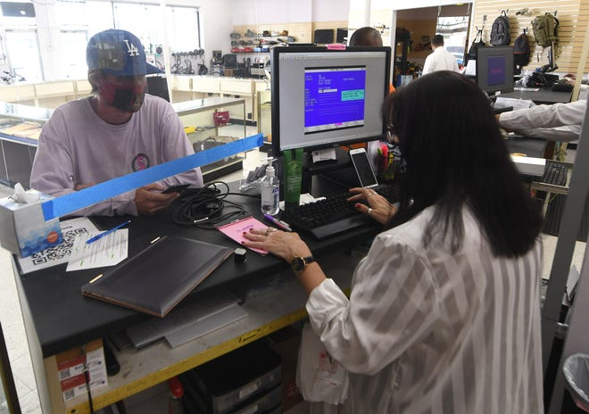 Robert Cutchin, left, pawns a laptop at National Pawn in Wilmington, N.C., Wednesday, September 1, 2021. The shop at 1702 Dawson St. opened in April after it had previously been Picasso Pawn.     MATT BORN/STARNEWS