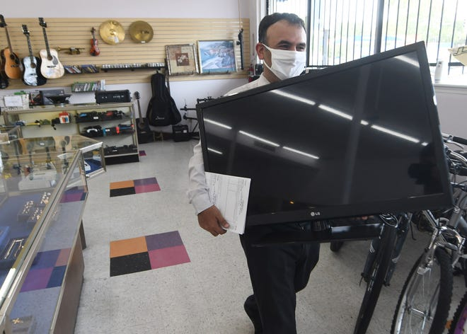 Pawnbroker Douglas Zelaya carries out a tv for a customer at National Pawn in Wilmington, N.C., Wednesday, September 1, 2021. The shop at 1702 Dawson St. opened in April after it had previously been Picasso Pawn.     MATT BORN/STARNEWS