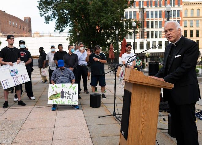 Rev. Richard Trainor leads a prayer during a vigil on International Overdose Awareness Day on Tuesday.