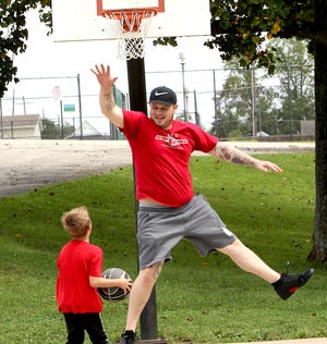 Andrew Fischman leaps in the air as he defends his son, Casey Deckard. The two were shooting baskets at the Thornton Park Basketball Courts Tuesday afternoon.