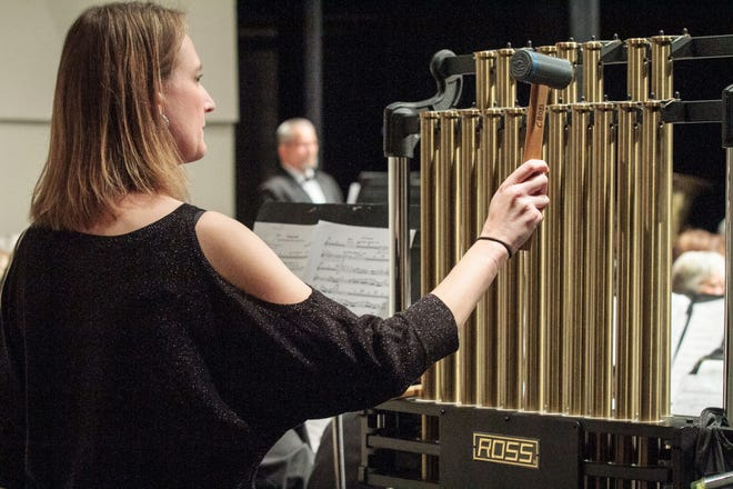 """Evie Tompkins strikes the chimes for the Community Band of Brevard. The band is """"Remembering the Past, Anticipating the Future,"""" with a Sept. 12 concert that honors tribute concert to the victims of 9/11 and the band's founder, the late Marion Scott. Photo---"""
