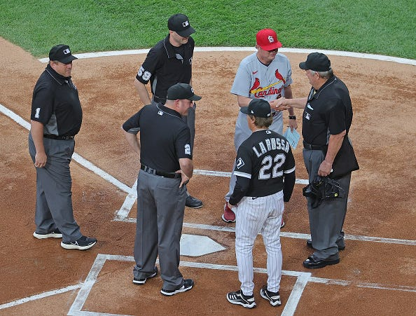 Umpire Joe West #22 and his crew Dan Bellino #2, Nic Lentz #59 and Bruce Dreckman #1 are greeted by manager Tony La Russa #22 of the Chicago White Sox and manager Mike Shildt #8 of the St. Louis Cardinals as West prepares to umpire a record breaking 5,367th game at Guaranteed Rate Field on May 25, 2021 in Chicago, Illinois.