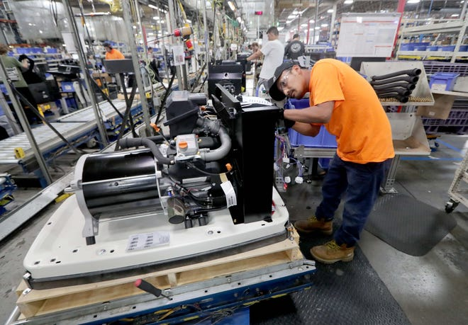 Generac employee Toribio Cruz works on assembling an air-cooled home standby generator at Generac in Whitewater. Generac has added hundreds of jobs in recent months and is busy making generators for Louisiana due to Hurricane Ida.