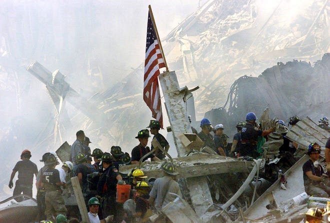 Rescue crews congregate near a U.S. flag amidst the rubble of the World Trade Center in New York in this September 13, 2001 file photo. September 11th marks the 20th anniversary of the 9/11 attacks where nearly 3,000 people died when four hijacked airliners were used in coordinated strikes on the Pentagon and the World Trade Center towers. The fourth plane crashed in Pennsylvania.