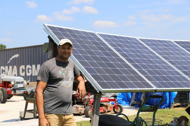 John Fraser poses in front of a solar panel array. Fraser and his wife Kelly began building their off-grid solar farm in 2016.