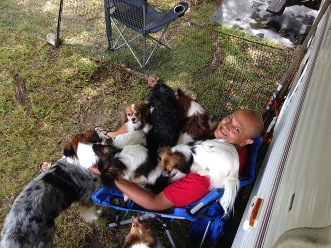 A photo of John Fraser and his dogs. Fraser said leaving behind his old life and disconnecting from money was the greatest decision he's ever made.