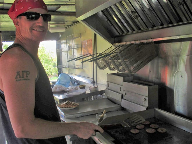 Patrick Payne is shown at the grill inside his food truck, the Green Chile Paddy Wagon, in September 2014.