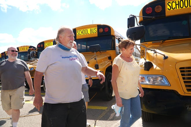 South Lyon School District bus driver trainer Cindy Dunn, right, leads a group of students through the school's depot on Sept. 1, 2021. From left are Chris Jackson, Mark Mitchell and (partially hidden) Tony Saks. All were training to become drivers for the school district.