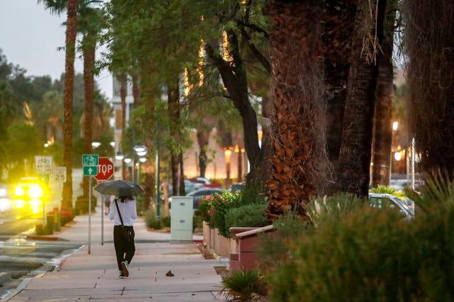 A pedestrian walks with an umbrella as rain drops begin to fall on South Belardo Road, Tuesday, Aug. 31, 2021, in Palm Springs.