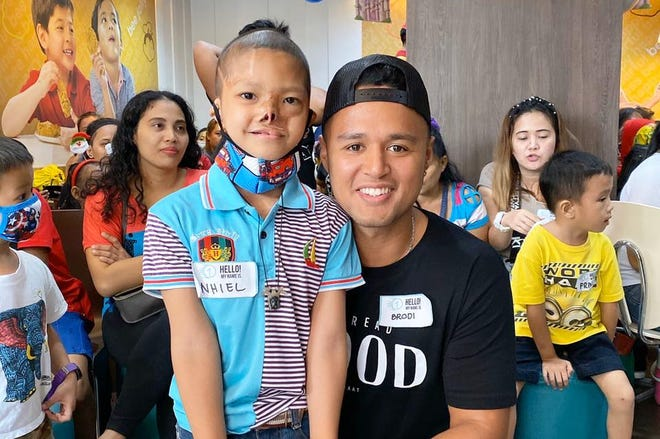 Campaign One at a Time founder Brodi Nicholas poses with a child in the Philippines.