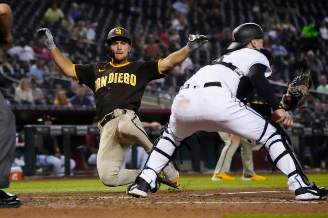 San Diego Padres' Adam Frazier, left, scores a run behind Arizona Diamondbacks catcher Carson Kelly on a ball hit by Jurickson Profar in the sixth inning during a baseball game, Tuesday, Aug. 31, 2021, in Phoenix. (AP Photo/Rick Scuteri)