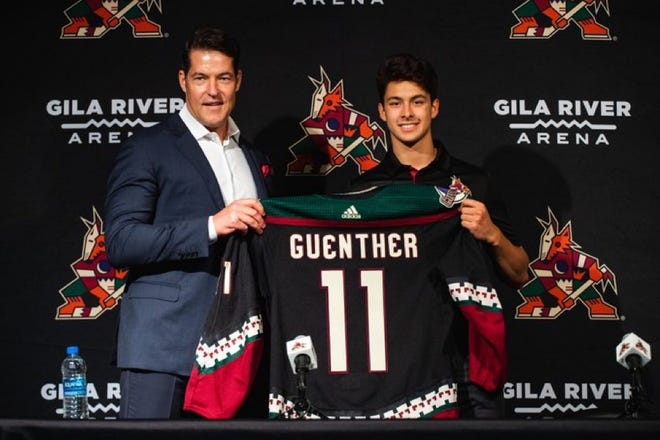 Coyotes 2021 top draft pick Dylan Guenther holds a team jersey with General Manager Bill Armstrong Wednesday at Gila River Arena.