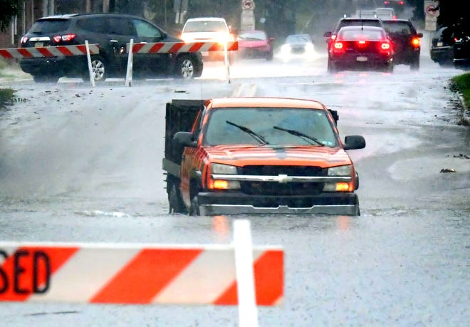 A vehicle maneuvers through a flooded roadway on North Belmont Street as rains from remnants of former Hurricane Ida soaked the region Wednesday, Sept. 1, 2021. Several roads were closed due to flooding during the day. Bill Kalina photo