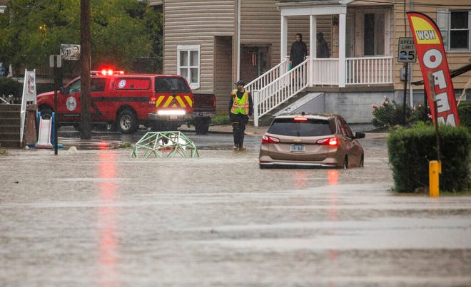 A car is stranded on a flooded street Wednesday, Sept. 1, 2021, in Bridgeville, Pa. Pennsylvanians braced for downpours and high winds from the remnants of Hurricane Ida, with forecasters warning that creeks, streams and rivers would be inundated across the state's southern tier. (Andrew Rush/Pittsburgh Post-Gazette via AP)