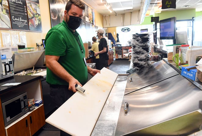 Health inspector Zack Van De Rostyne checks the cleanliness of a food preparation table on Wednesday, September 1, 2021 at Camille's Sidewalk Cafe in Sioux Falls.