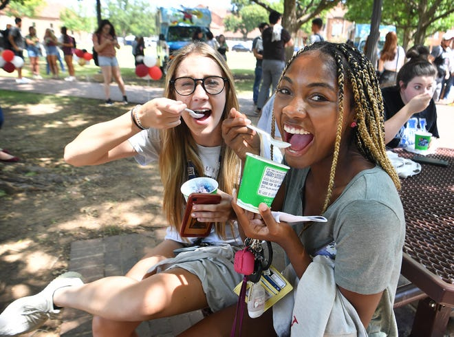 Midwestern State University students Makenna Gaenzle, left, and Jewel Lewis enjoy their free sno-cones during a celebration of the new partnership between MSU Texas and Texas Tech University which went into effect Wednesday.