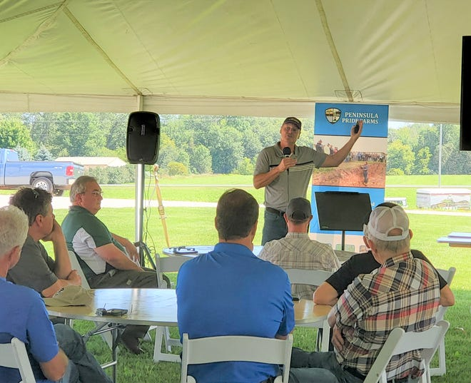 """Rick Clark, a cash crop farmer from Indiana, talks with participants at a field day hosted by Peninsula Pride Farms on Aug. 17 in Kewaunee, Wis. Clark has been celebrated by national groups for an innovative approach to soil health that he calls """"Farming Green."""""""
