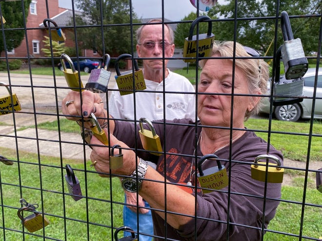 Ida Lussier hangs locks in honor of her sons, Jim and Justin Ingher, who died of overdoses two years ago. Jim was 41, and Justin 49. Lussier's boyfriend, Terry Fitz, also placed a lock on the fence outside of Cairn Recovery Resources in memory of his son, Matt Fitz, who died last year at the age of 44.
