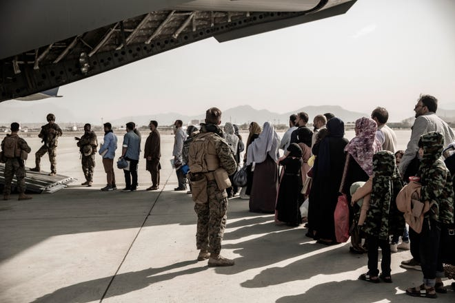 The U.S. Marine Corps and evacuees wait to board a Boeing C-17 Globemaster III during an evacuation at Hamid Karzai International Airport in Kabul, Afghanistan.