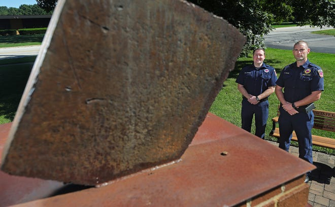 Tallmadge firefighter Kyle Morrow, left, and Deputy Fire Chief Ben Stasik pose for a photo in Tallmadge next to a chunk of steel beam from the World Trade Center.