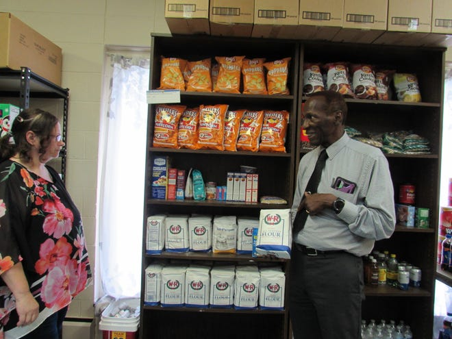 The Rev. David A.E. Whitt of Faith United Methodist Church talks to  Michelle Amtsberg about the pantry items at the church. Whitt said many people may be surprised that flour is an item available through the church's pantry.