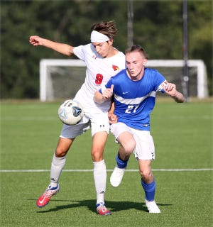 Boonville's Caleb Martin battles for the ball against a Clinton player in the first half Tuesday night in the season opener for both teams at the Boonville City Soccer Field. The Pirates fell to Clinton 3-0.