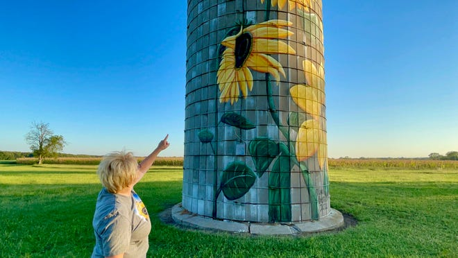 Diana Burress points to her favorite sunflower on the silo painted on her farm.