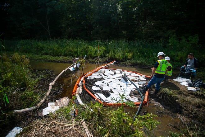 The Ohio Department of Natural Resources uses special towel-like material that is designed to soak up oil, but not water, as they work to contain and plug a crude oil spill at Veto Lake, likely from an old orphaned well, in Washington County on Aug. 23.