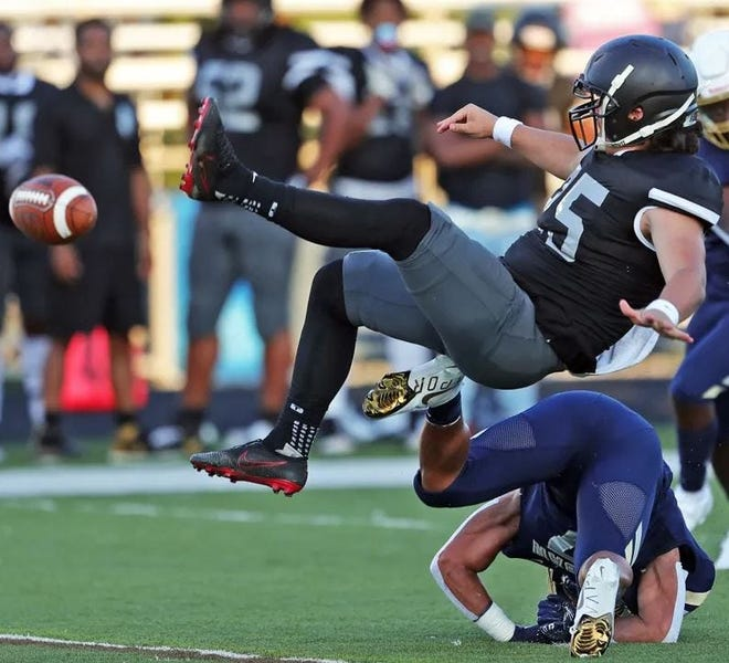 A Bishop Sycamore punter is upended during a football game against Akron Archbishop Hoban, Thursday, Aug. 19, 2021, in Akron, Ohio.  Bishop Sycamore