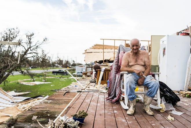 William Duplantis enjoys the breeze outside on the porch sitting between the remnants of his home at Grand Caillou.