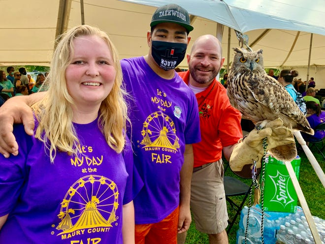 Animalogist Bob Tarter, right, brings his eagle owl, Elle, up close with William Scott and Misty Rickett during My Day at the Maury County Fair.