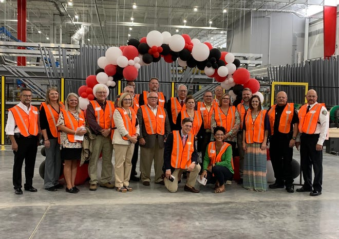 Mohawk Industries in Thomasville recently completed a 275,000-square-foot addition and is adding 50 jobs to its workforce. Pictured are Mohawk employees and Thomasville officials.