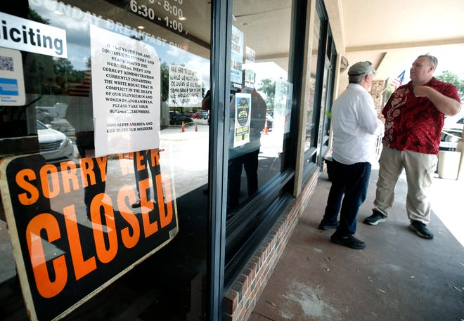 """Two customers discuss Afghanistan outside the DeBary Diner on Thursday. The business was closed after a crush of customers came Wednesday in support of the note seen on the door asking supporters of Joe Biden to """"take your business elsewhere."""""""